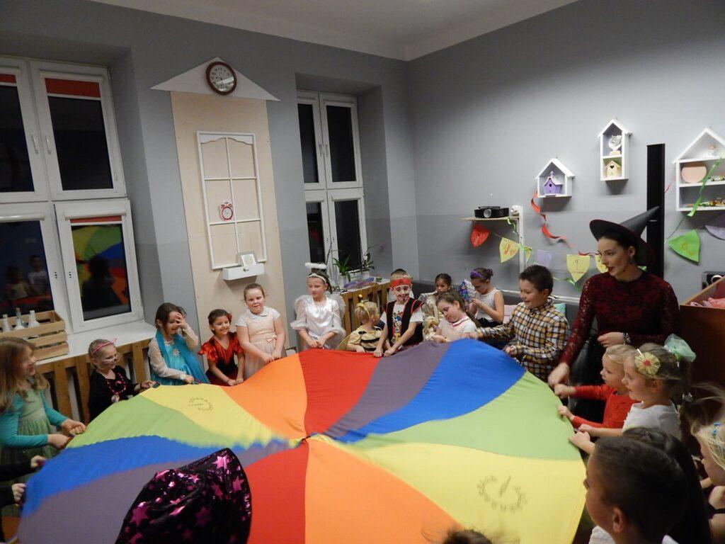 Zdjęcie przedstawia dzieci podczas zabawy Andrzejkowej trzymające kolorowe koło w pomieszczeniu z szarymi ścianami.