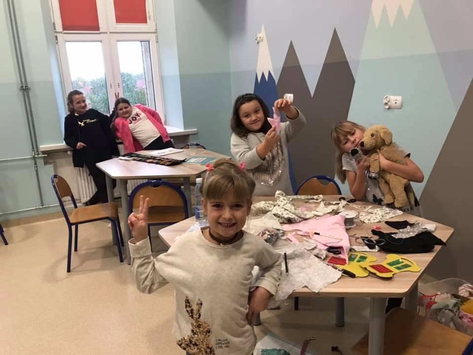 Obraz przedstawia dzieci w placówce, które tętnią radością wykonując różnego rodzaju prace plastyczne.