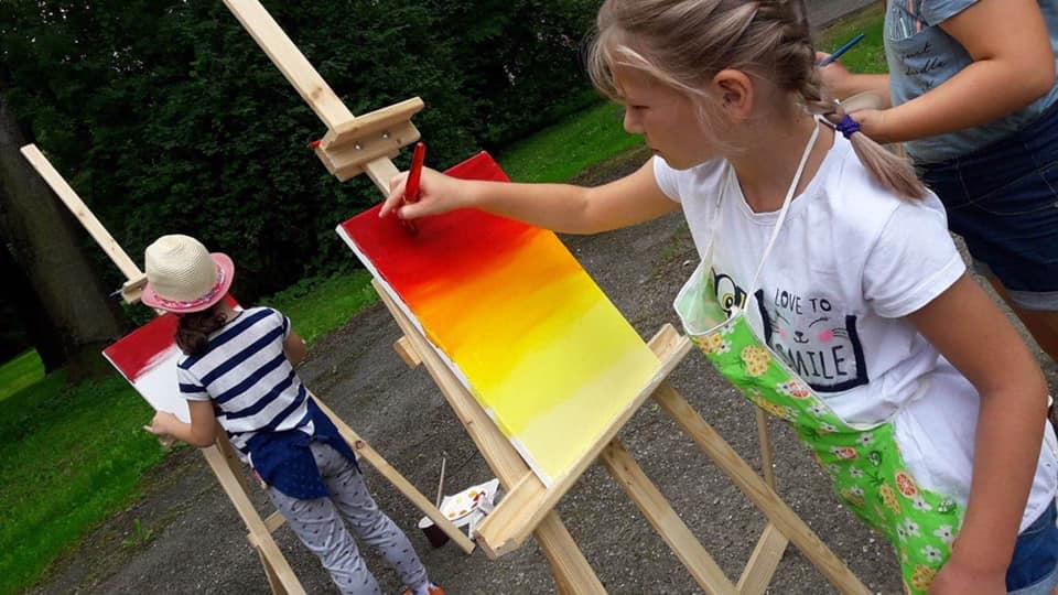 Obraz przedstawia malujące dzieci przy użyci akryli.