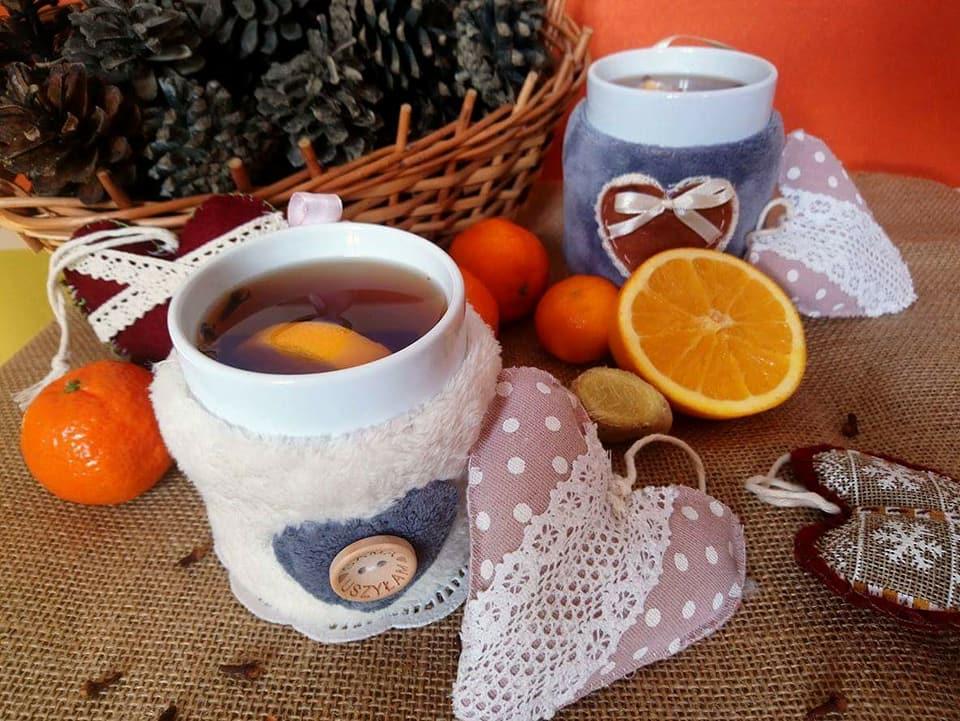Zdjęcie ozdobne z ozdobionymi kubkami herbaty, a na tle koszyk z szyszkami.