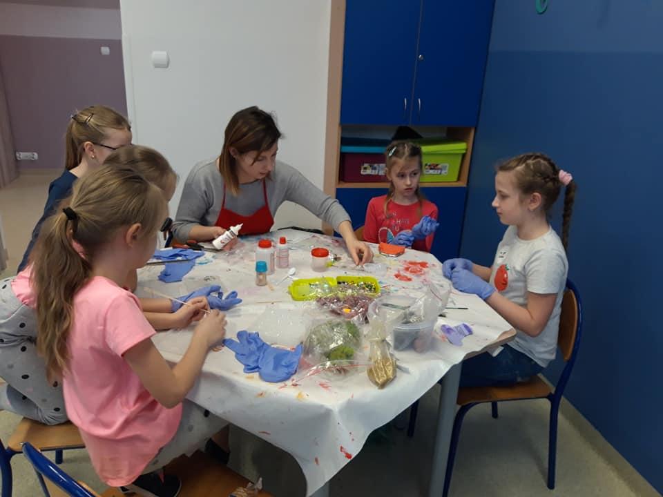 Obraz przedstawia zajęcia artystyczne. Podczas których wychowankowie z wychowawczynią tworzą rękodzieła z żywicy epoksydowej. Na zdjęciu możemy ujrzeć dzieci siedzące przy stole z wychowawczynią oraz różnego rodzaju materiały do tworzenia przepięknych prac.