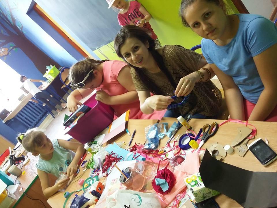 Zdjęcie przedstawia dzieci i pracowników placówki przy stole robiących rękodzieła.