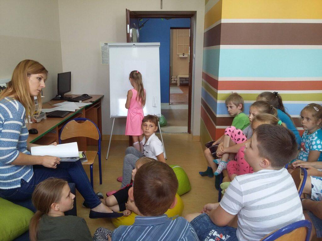 Zdjęcie przedstawia dzieci z placówki oraz osobę prowadzącą zajęcia w pokoju z kolorowymi ścianami.