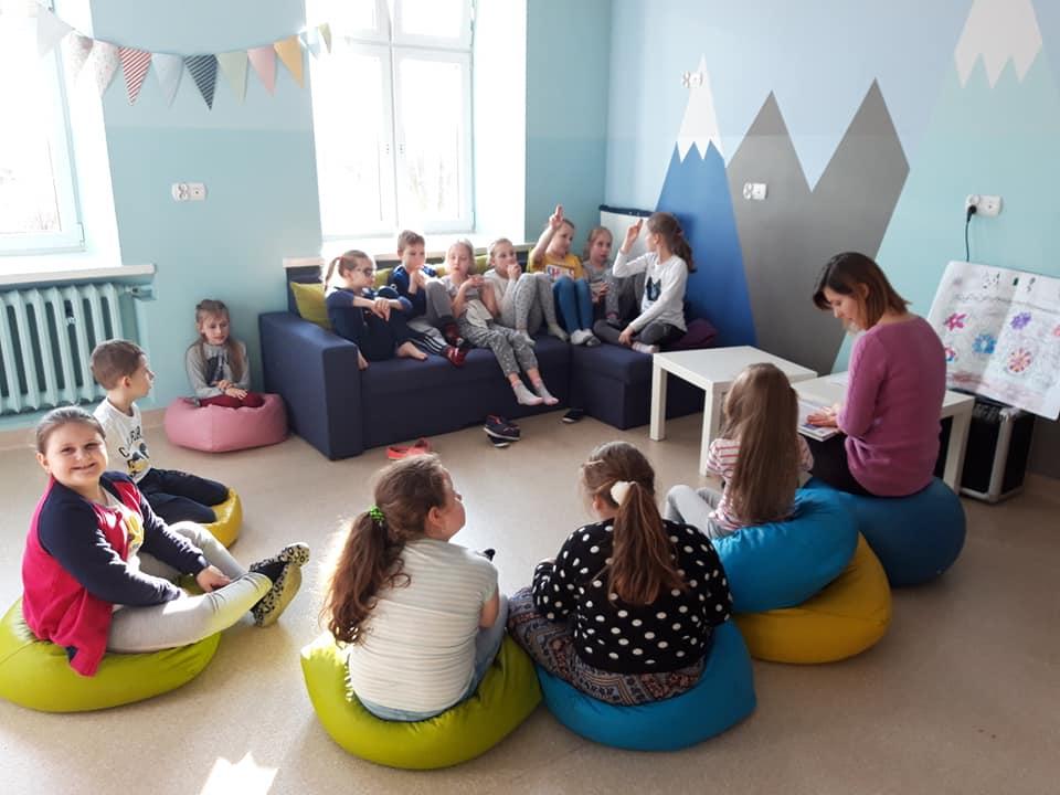 Obraz przedstawia zajęcia psychoedukacyjne. Na zdjęciu możemy ujrzeć dzieci słuchające wychowawczyni,  siedzące na sofie oraz poduszkach.