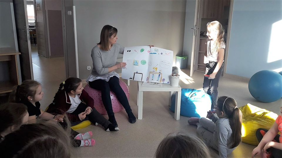 Obraz przedstawia zajęcia psychoprofilaktyczne. Na zdjęciu możemy ujrzeć dzieci z wychowawczynią, trzymająca rysunek jednej z wychowanek.