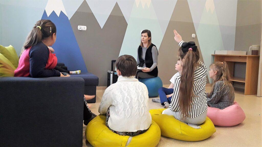 Obraz przedstawia wychowanków SPWD podczas ćwiczeń inteligencji emocjonalnej. Na zdjęciu możemy ujrzeć dzieci siedzą na poduszkach oraz sofie.