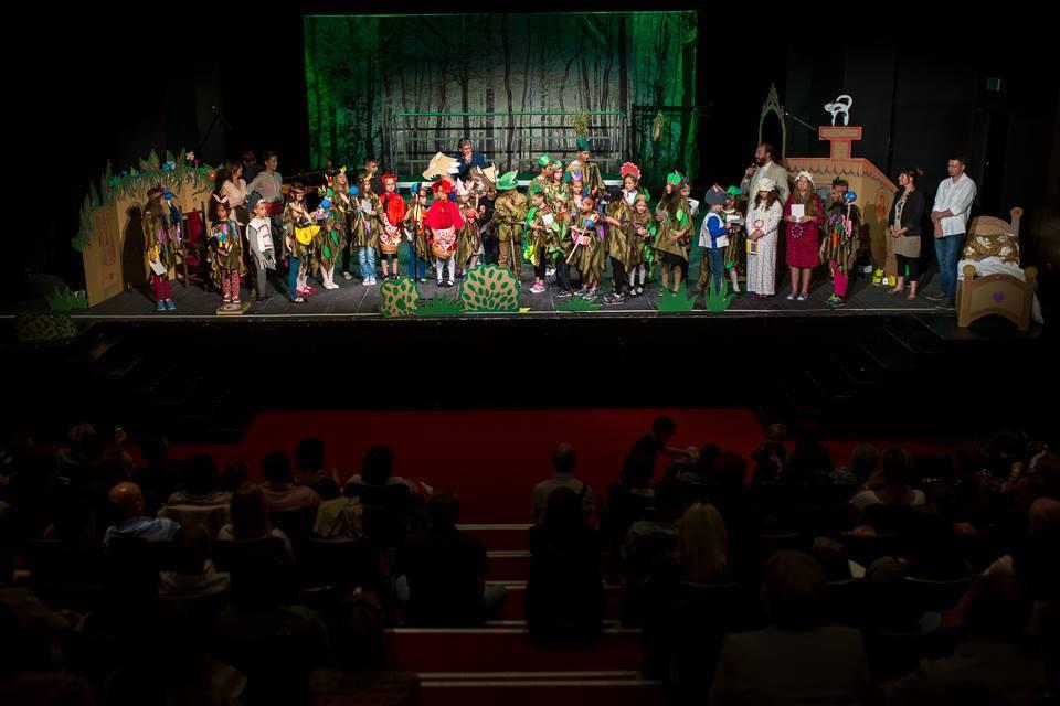 Zdjęcie przedstawia dzieci z placówki na scenie teatru w Tarnowie, natomiast na sali widnieje publiczność.