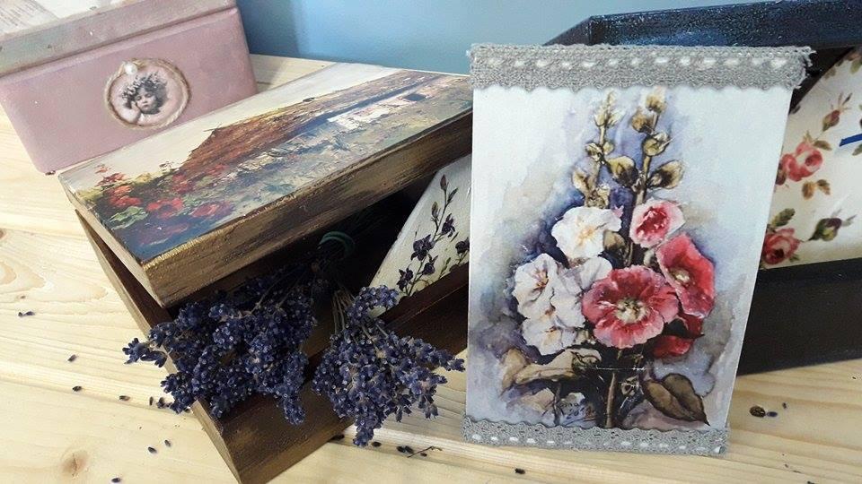 Zdjęcie przedstawia rękodzieła takie jak skrzynie oraz obraz kwiatów udekorowany wstążkami.
