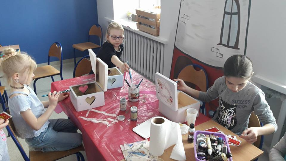 Obraz przedstawia wychowanków SPWD podczas warsztatów artystycznych. Na zdjęciu można ujrzeć proces tworzenia drewnianych skrzyneczek.