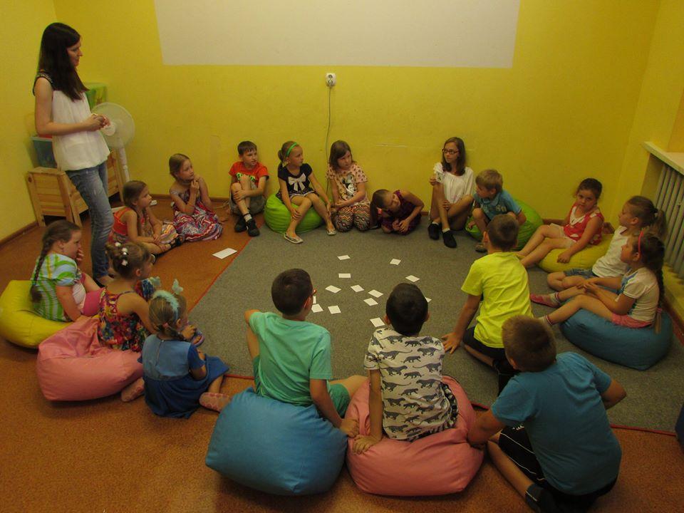 Zdjęcie przedstawia dzieci z placówki siedzących w okręgu podczas zajęć w sali z zielonymi ścianami.