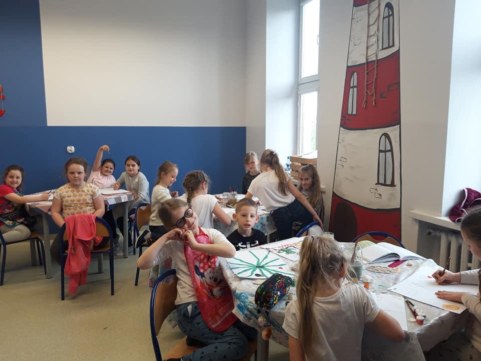 Obraz przedstawia naszych wychowanków podczas zajęć z bezpieczeństwa w internecie. Na zdjęciu widzimy dzieci siedzące przy stołach na których wykonują rysunki.