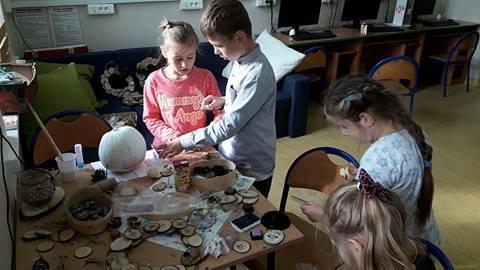 Zdjęcie przedstawia dzieci tworzące dekorację z rzeczy znalezionych w lesie, np. szyszki, mech, itd.