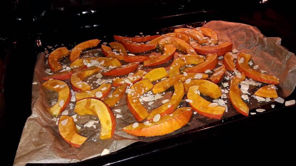 Obraz przedstawia kawałki dyni z miodem i migdałami w piekarniku.