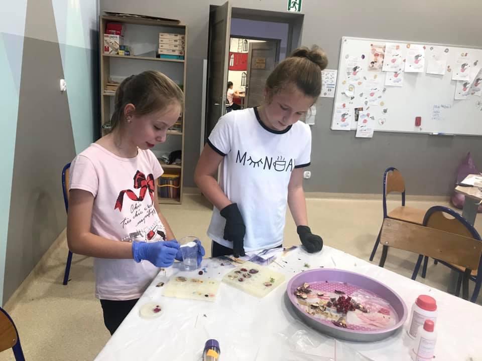 Obraz przedstawia dzieci wykonujące różne prace z żywicy epoksydowej.