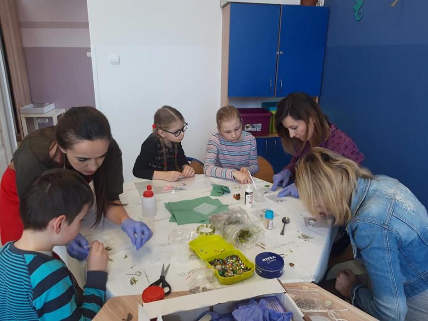 Obraz przedstawia wychowanków SPWD podczas zajęć z wykorzystaniem żywicy epoksydowej. Na zdjęciu możemy ujrzeć dzieci z wychowawczyniami przy stole, na którym powstają przepiękne ozdoby.
