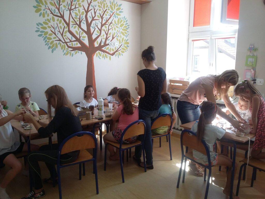 Zdjęcie przedstawia dzieci siedzące przy stolikach w sali z namalowanym drzewem