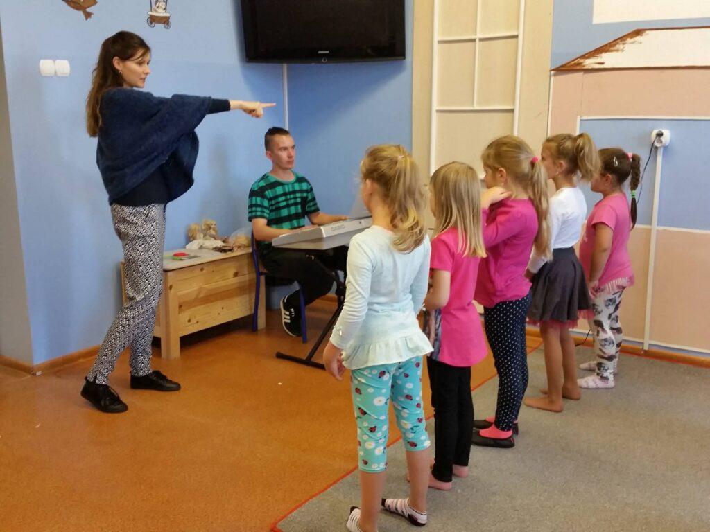 Zdjęcie przedstawia dzieci ustawione w rzędzie w pomieszczeniu z niebieskimi ścianami przygotowujące się wraz z opiekunami do muzycznego występu.