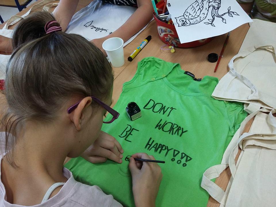 """Obraz przedstawia dziewczynkę malującą na zielonej koszulce położonej na stole napis """"Dont worry, be happy!"""""""
