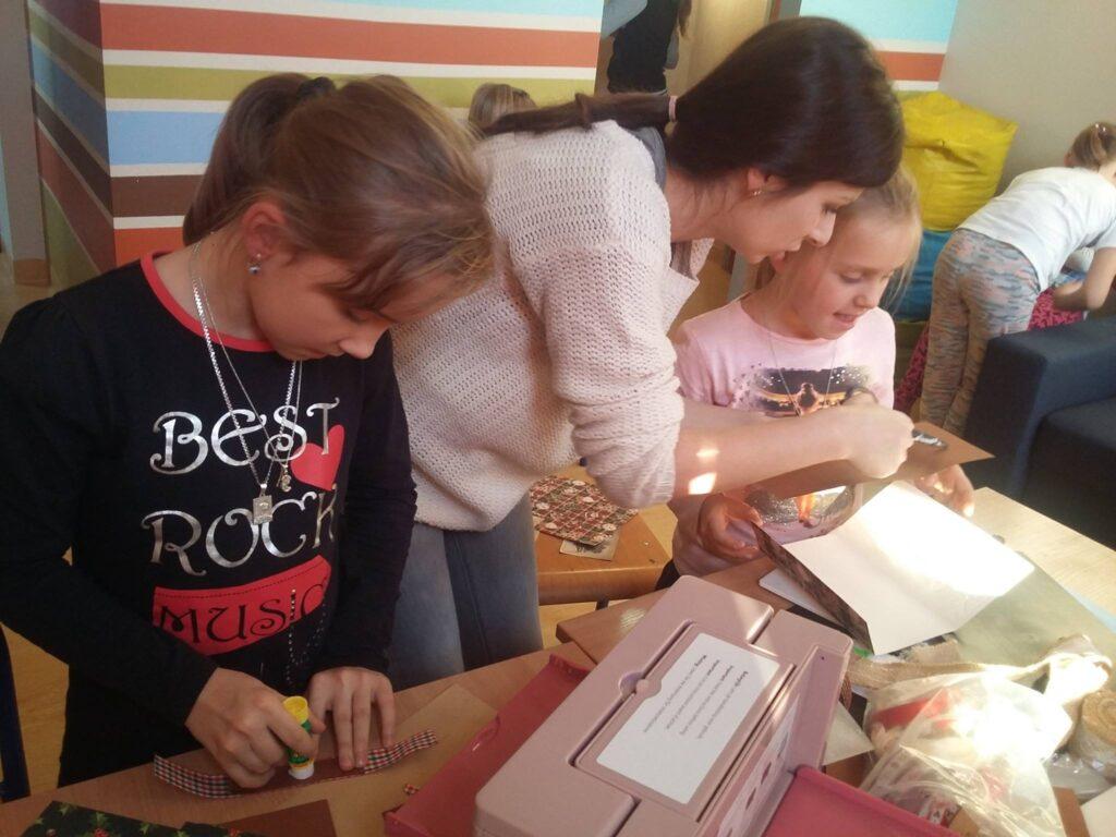 Zdjęcie przedstawia dzieci wraz z osobą prowadzącą zajęcia przy stole tworzące rękodzieła w ramach krainy rozmaitości.
