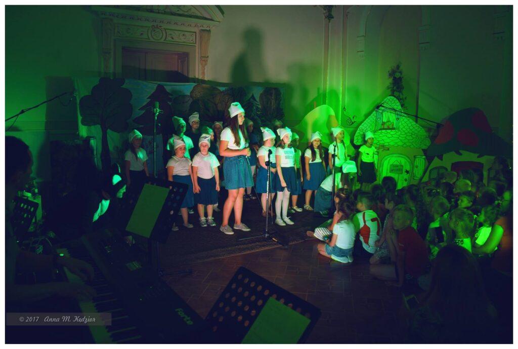 """Zdjęcie przedstawia dzieci podczas występu """"Kto pod kim dołki kopie"""" w otoczeniu publiczności i zielonego światła."""