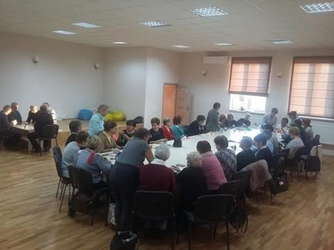 Zdjęcie przedstawia dużą ilość osób siedzących wokół dużego stołu w białym, dobrze oświetlonym pokoju.