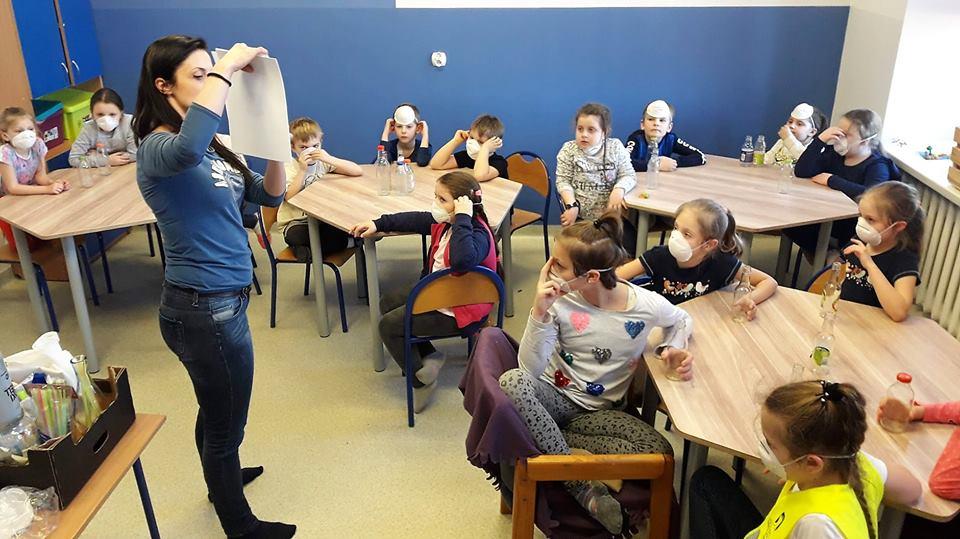 Obraz przedstawia wychowanków podczas zajęć z wykorzystaniem małego laboratorium. Na zdjęciu możemy ujrzeć dzieci siedzące przy stołach na których znajdują się przedmioty potrzebne do wykonania eksperymentów.
