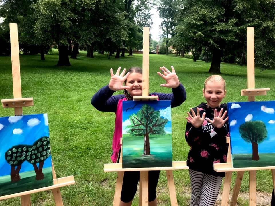 Obraz przedstawia dzieci wraz z swoimi obrazami wykonanymi przy użyciu akryli.