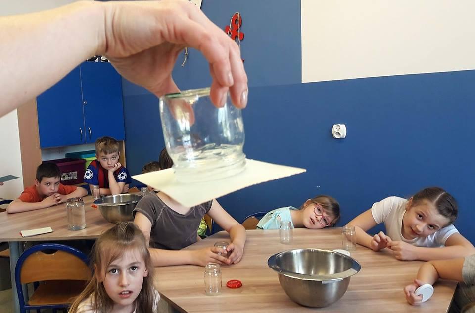 Obraz przedstawia wychowanków podczas zajęć których tematem były żywioły ziemi. Na zdjęciu możemy ujrzeć zaciekawione dzieci, aktualnym eksperymentem. Wychowankowie siedzą przy stołach, na których są przygotowane przedmioty do doświadczeń.