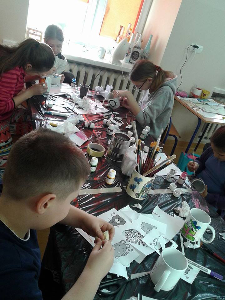 Zdjęcie przedstawia dzieci z placówki przy stole z czarnym nakryciem malujące na porcelanie.