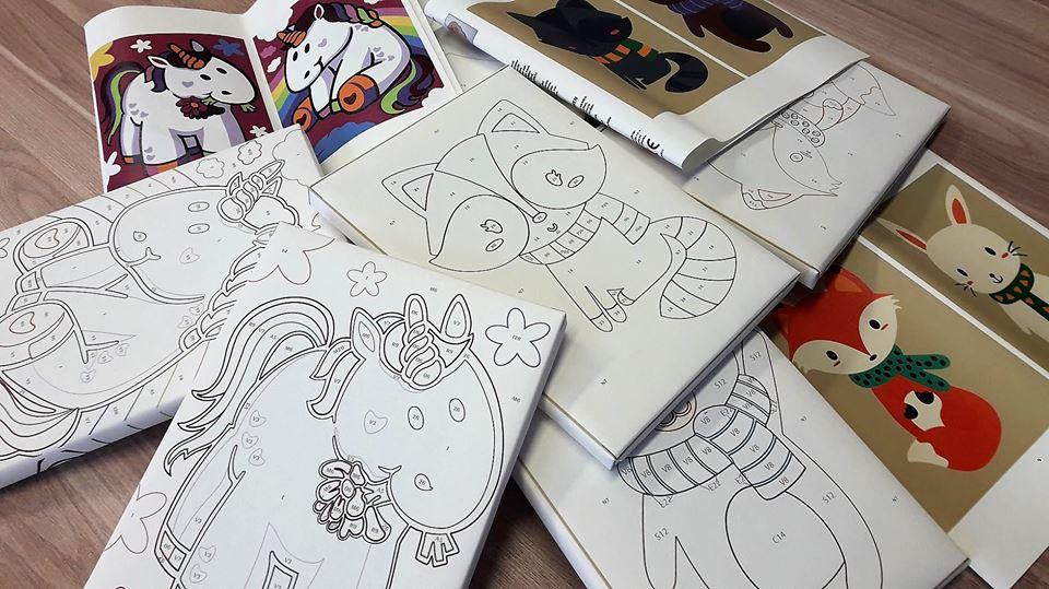 Obraz przedstawia prace wykonane za pomocą malowania po numerach. Na zdjęciu możemy ujrzeć liski, koniki, czy króliki.