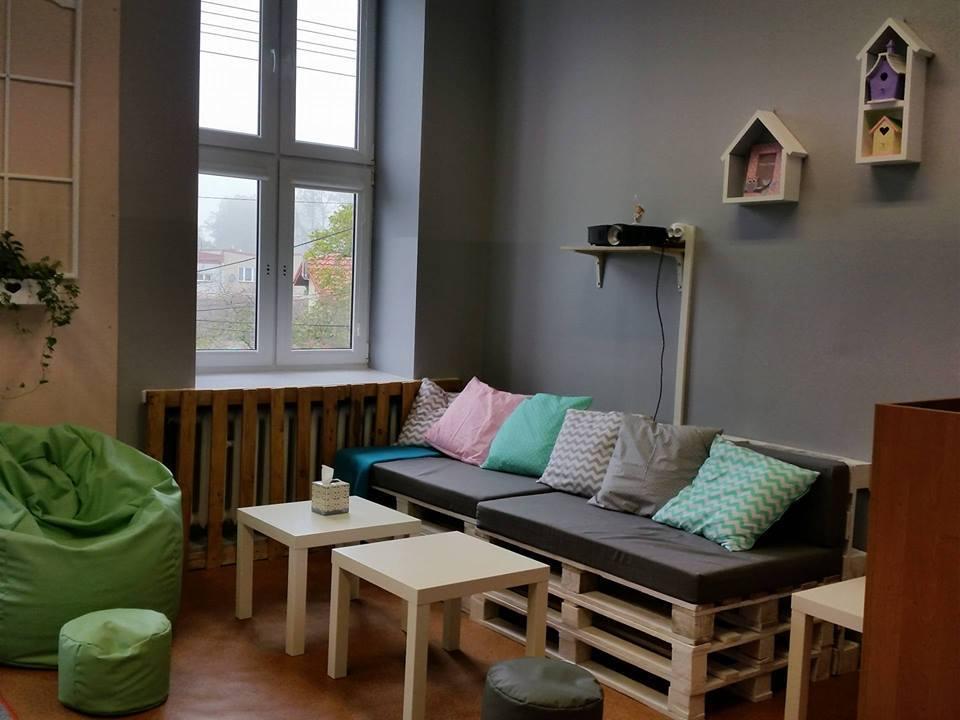 Na zdjęciu widnieje odnowiony pokój w SPWD w Radłowie. Pomieszczenie zawiera: zielone siedzisko dla dzieci, 2 stoliki, kanapa z palet, kilka poduszek na niej, ściany są koloru szarego z powieszonymi półkami w kolorze białym, dodatkowo poczwórne okno.