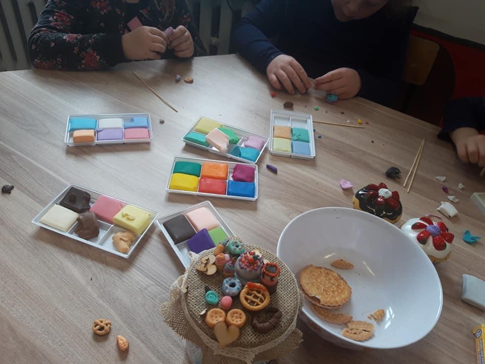 Obraz przedstawia modelinowe wypieki naszych wychowanków. Na zdjęciu możemy ujrzeć proces powstawania modelinowych ciastek.