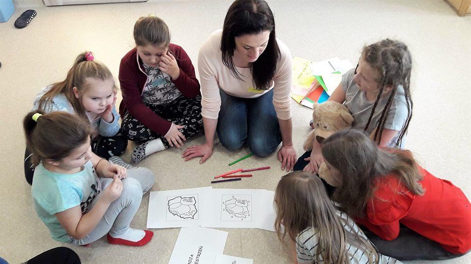 Obraz przedstawia wychowanków podczas zajęć socjoterapeutycznych. Na zdjęciu możemy ujrzeć wychowanków, wychowawczynię oraz kartki na których namalowany jest kontur Polski.