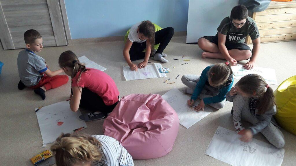 Obraz przedstawia wychowanków SPWD podczas warsztatów relaksacyjnych. Na zdjęciu możemy ujrzeć dzieci rysujące muzykę.