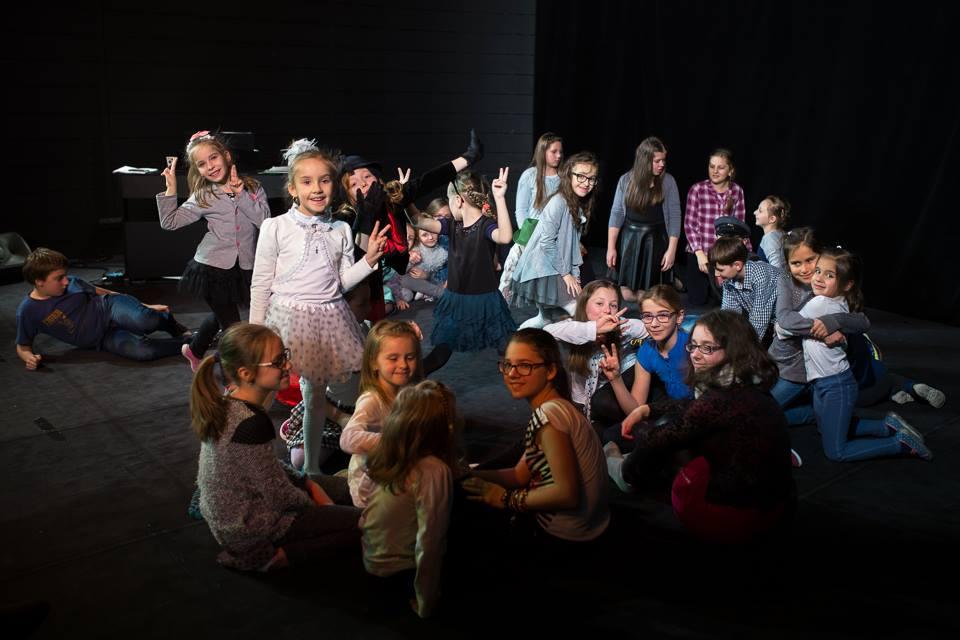Zdjęcie przedstawia dzieci z placówki podczas przygotowania do występu na scenie teatralnej.