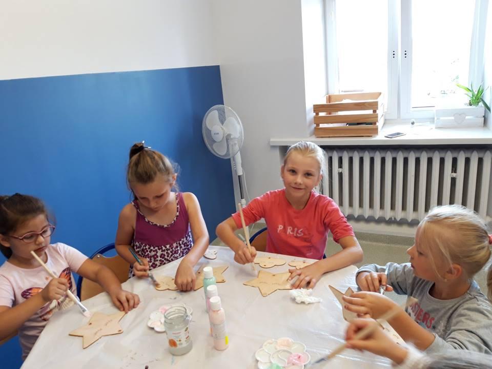 Obraz przedstawia wychowanków SPWD podczas warsztatów artystycznych. Na zdjęciu możemy ujrzeć proces powstawania drewnianych dekoracji.