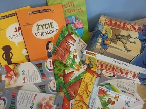 Zdjęcie przedstawia kredki, książki oraz gry planszowe rozłożone na stole.