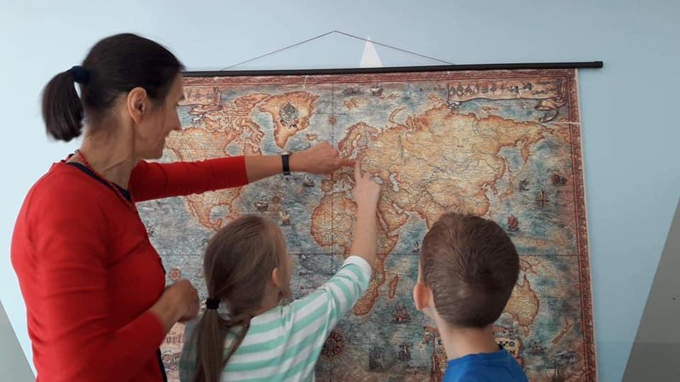 Obraz przedstawia naukę geografii w placówce przy użyciu mapy świata.