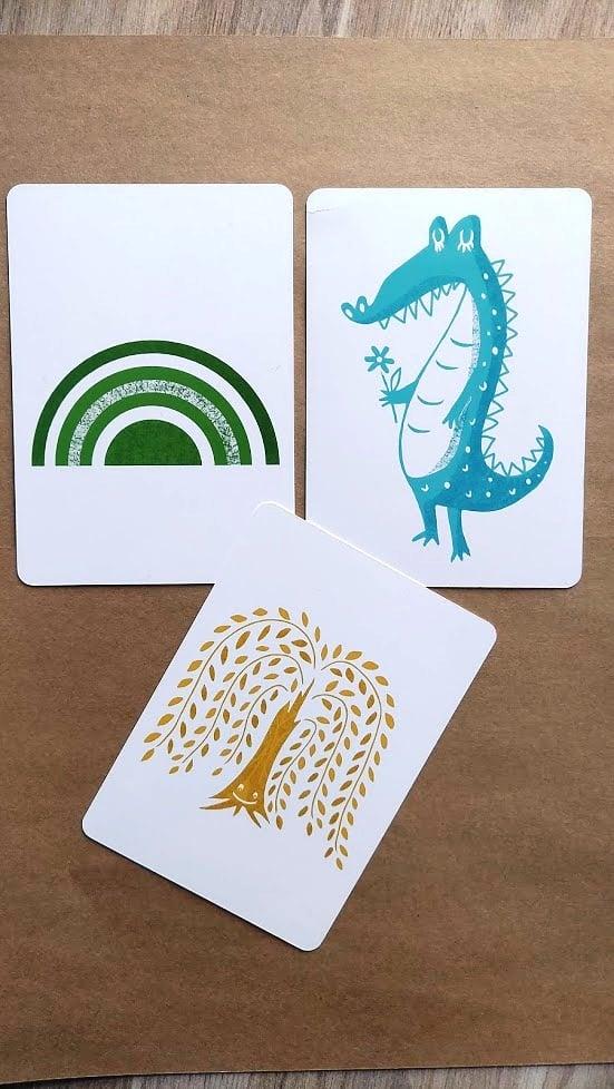 Obraz przedstawia karty wspierające regulację emocji. Na każdej z kart możemy ujrzeć jakiś obrazek w danym kolorze, karta niebieska przedstawia krokodyla, karta zielona tęczę oraz karta żółta wierzbę.