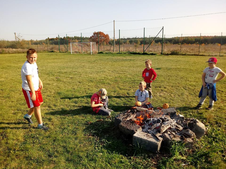 Obraz przedstawia wychowanków oraz ognisko na boisku.