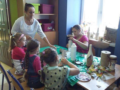 Zdjęcie przedstawia dzieci oraz opiekunów z placówki podczas zajęć manualnych, podczas których dzieci robiły ciekawe ozdoby.