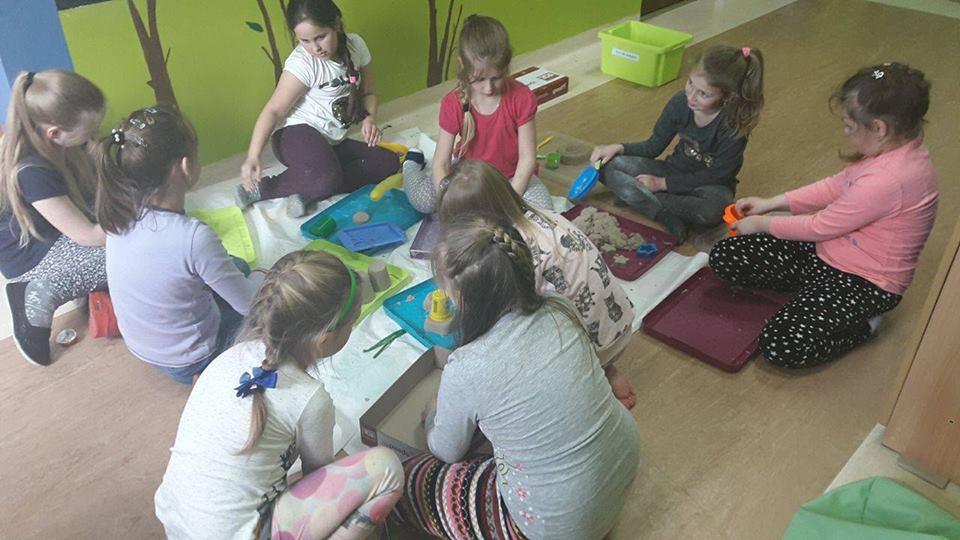"""Zdjęcie przedstawia dzieci bawiące się w """"domowej piaskownicy"""" na podłodze w pokoju placówki SPWD."""