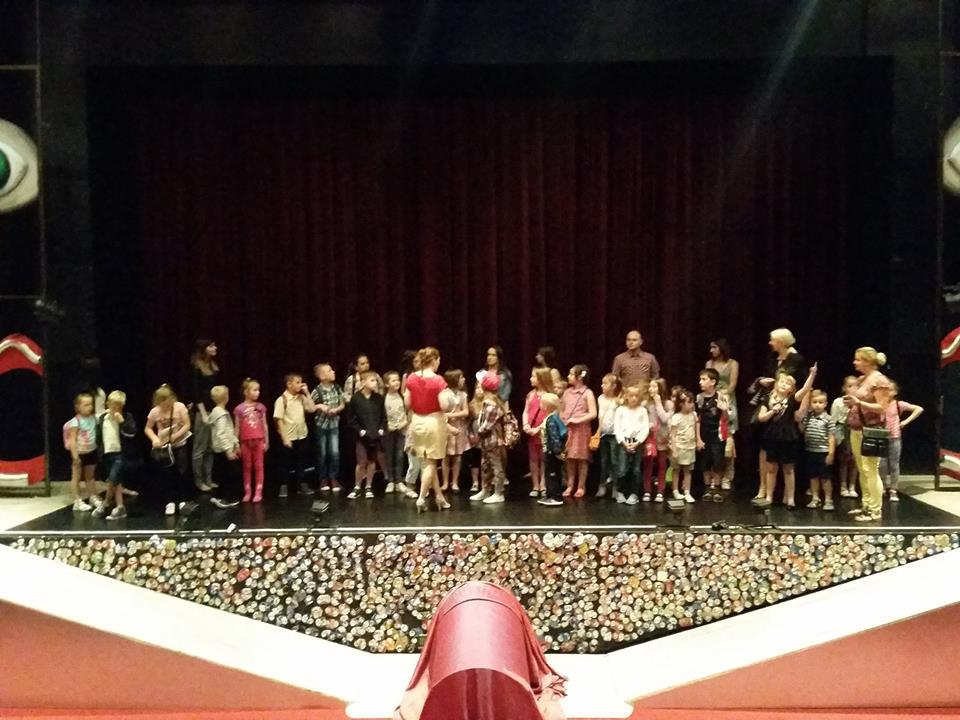 """Zdjęcie przedstawia dzieci na scenie teatru z aktorami tuż po spektaklu pt. """"Pinokio"""", na który dzieci zostały zaproszone."""
