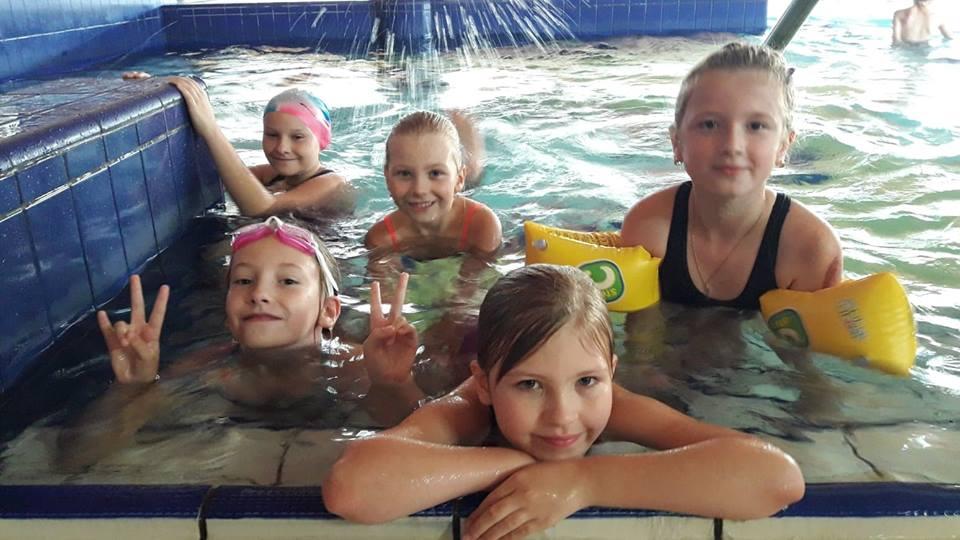 Obraz przedstawia wychowanków SPWD podczas nauki pływania. Na zdjęciu możemy ujrzeć dzieci w basenie.