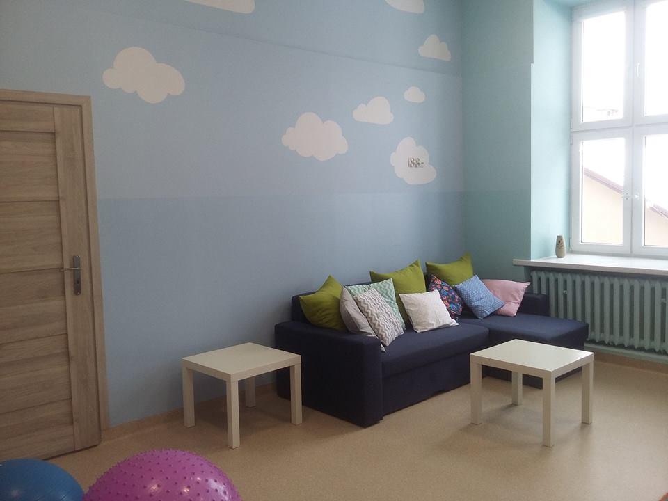 Obraz przedstawia wyremontowaną placówkę SPWD. Na zdjęciu widzimy sofę z poduszkami oraz stoliczki.