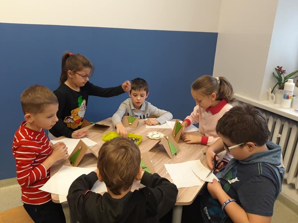 Obraz przedstawia wychowanków podczas zajęć artystycznych. Na których pracują przy użyciu techniki scrapbookingu wykonując kartki piankowo-brokatowe.