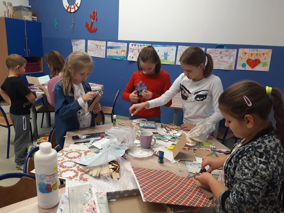 Obraz przedstawia wychowanków SPWD podczas wykonywania dekoracji na kiermasz świąteczny.