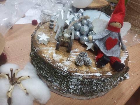 Obraz przedstawia pień drzewa ozdobiony przy użyciu sztucznego śniegu, na którym znajdują się m.in. szyszki, gwiazdki, bombki, czy Aniołek.