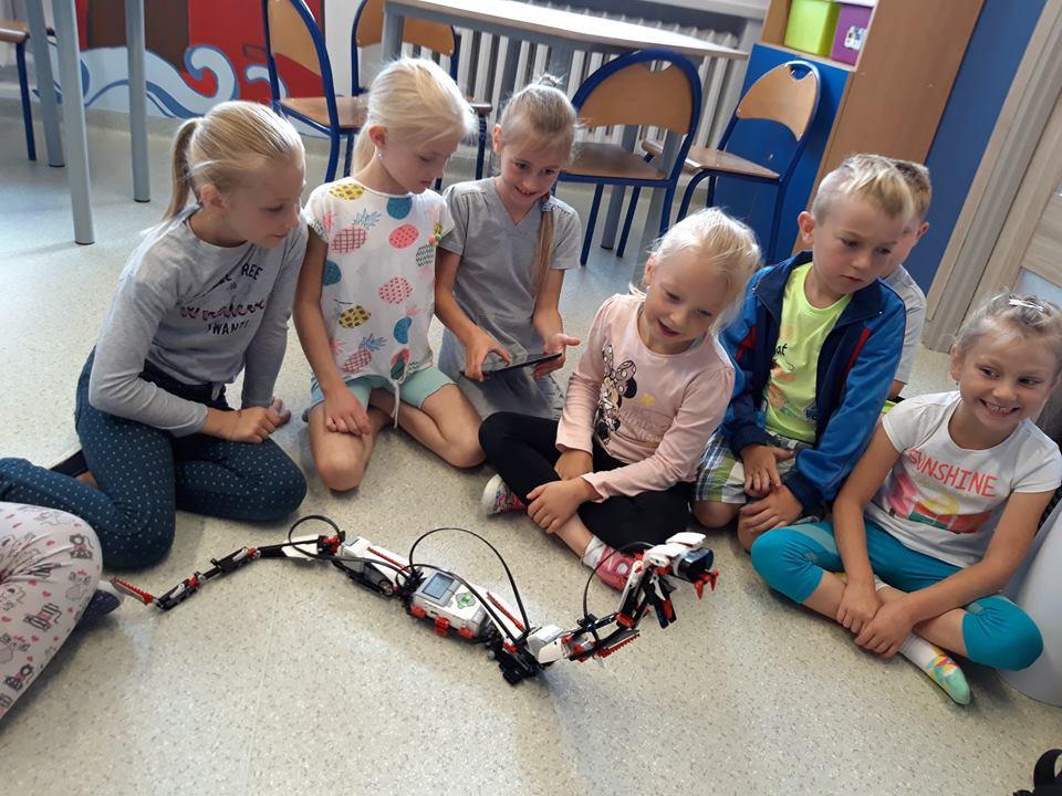 Obraz przedstawia warsztaty z robotyki. Na zdjęciu możemy ujrzeć dzieci zainteresowane robotem przypominającego węża.