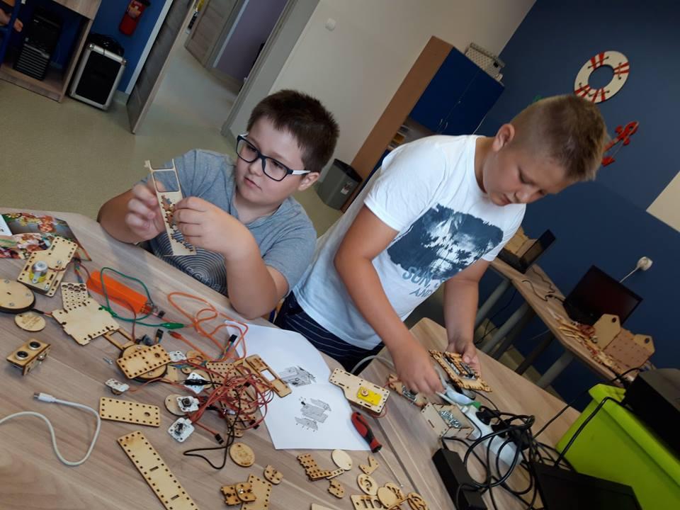 Obraz przedstawia warsztaty robotyki. Na zdjęciu możemy ujrzeć dzieci, które tworzą roboty.
